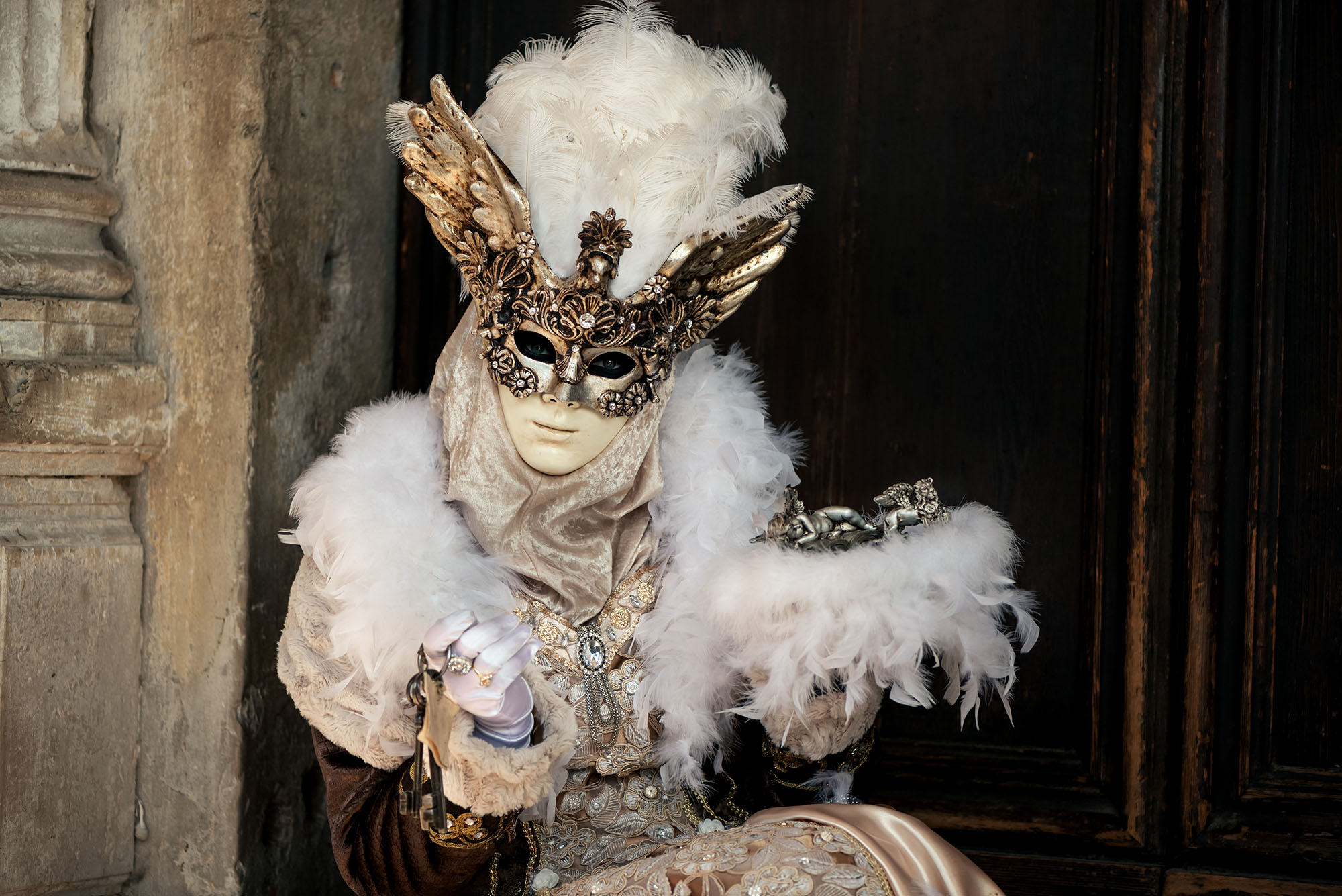 woman in Venetian carnival costume against the wall