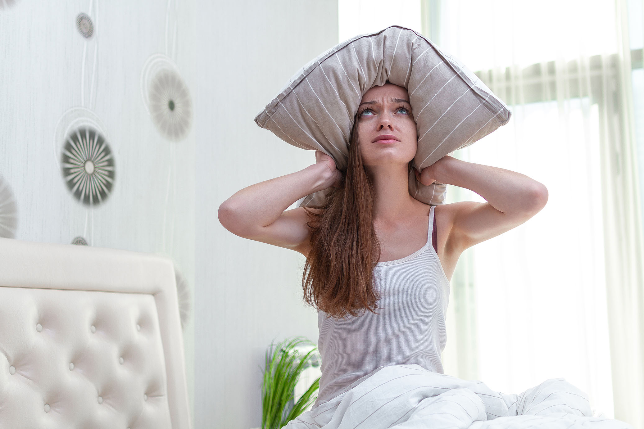 sad-woman-suffering-disturbed-by-noisy-neighbors-covering-her-ears-with-pillow
