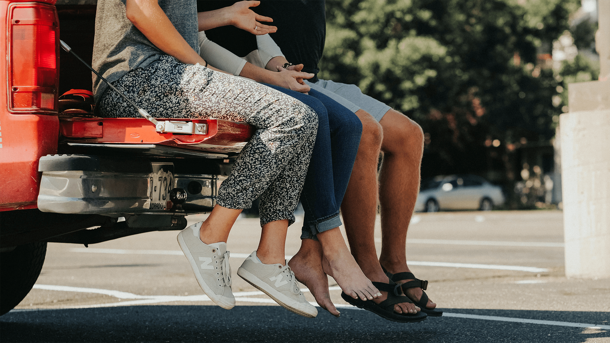 three people legs and shoes visible sitting on edge of car trunk
